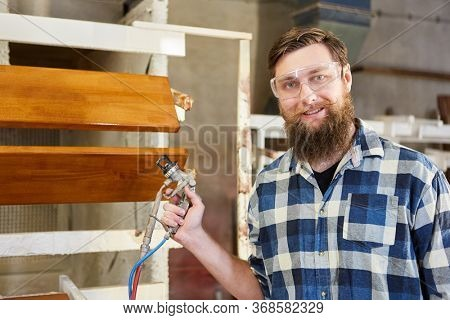 Carpenter as a painter with the spray gun in the carpentry or paint shop