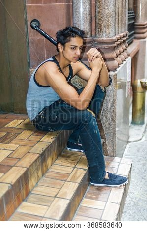 Serious East Indian American Male Teenager Thinking Outside In New York City, Wearing Gray Tank Top,