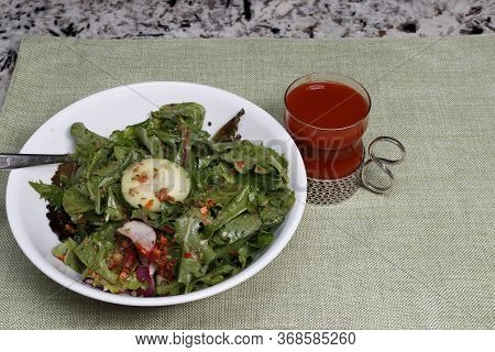 Healthy Spring Mix Salad In A Bowl With Vegetables And Carrot Ginger Salad Dressing And Tomato Juice