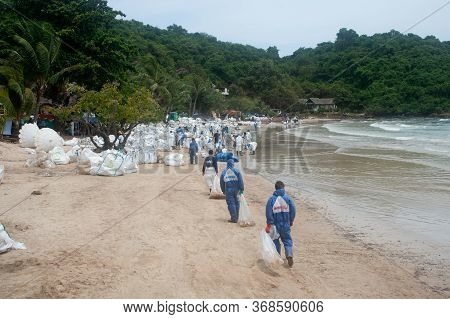 Rayong,thailand-february 8,2013 : Unidentified Workers And Volunteers Are Shoveling Sand With Crude