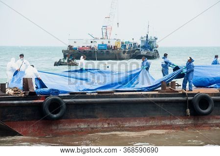 Rayong,thailand-february 8,2013 :   Workers And Volunteers Laying Large Plastic Sheets On A Crude Oi