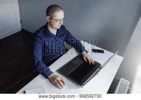 The Man Is Sitting By The Table And Working At Home On Laptop. Man In Quarantine Working From Home.