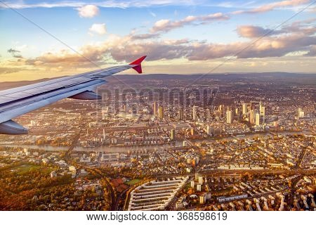 Airplane window view to the city at sunset