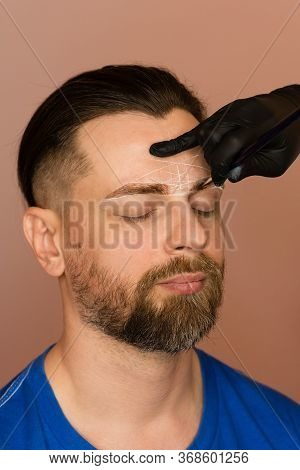Permanent Makeup For Eyebrows. Tinting Brows. Handsome Man With Eyebrows In Barber Shop. Brutal Male