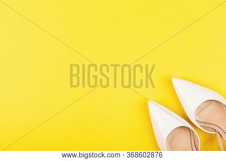 White Female Fashion Shoes On Yellow Background. Flat Lay Top View Copy Space. Fashion Blog Or Magaz