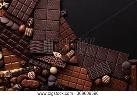 Pile Chocolate Bars And Candies Background, Sweet Confection For Dessert.