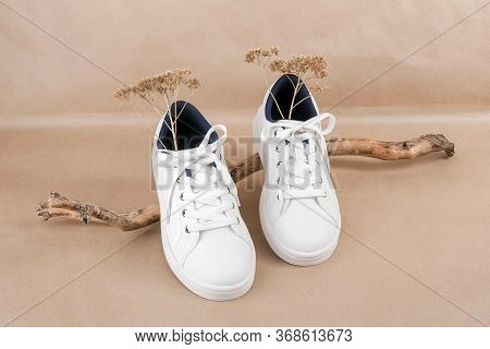 Ethical Vegan Shoes Concept. A Pair Of White Sneakers On The Wooden Snag, Neutral Beige Craft Paper