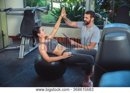 Personal Trainer Working With Client In Gym. Trainer Man Helping Young Woman With Fitness Ball Worko