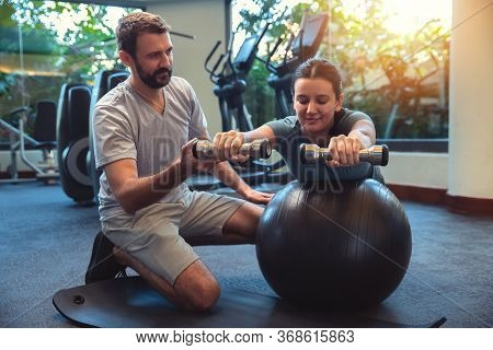 Personal Trainer Working With Client In Gym. Trainer Man Helping Young Woman With Her Work Out With