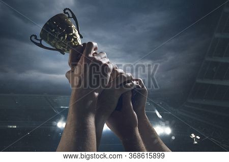 Hard Work. Award Of Victory, Male Hands Tightening The Golden Cup Of Winners Against Cloudy Dark Sky