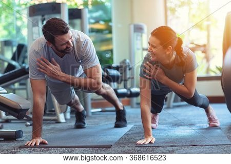 Couple Exercise Together In Gym. Man And Woman Working Out In Fitness Club Doing Plank Exercise. Hea