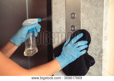 Hands In Blue Rubber Gloves Cleaning And Disinfecting Elevator Buttons Using Alcohol Sanitizer Spray