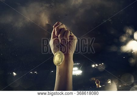 Champion. Award Of Victory, Male Hands Tightening The Golden Medal Of Winners Against Cloudy Dark Sk