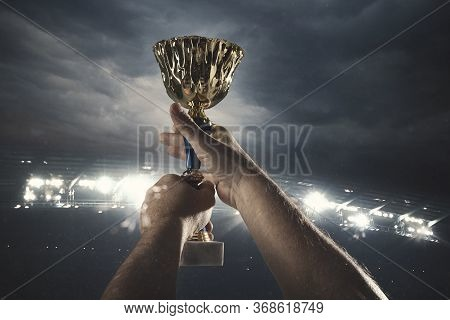 Dream Comes True. Award Of Victory, Male Hands Tightening The Golden Cup Of Winners Against Cloudy D