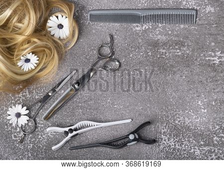 Top View Of Hair Salon Set With Blond Strands Of Hair On Gray Background, Space For Text