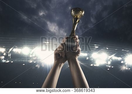 Winner Way. Award Of Victory, Male Hands Tightening The Golden Cup Of Winners Against Cloudy Dark Sk