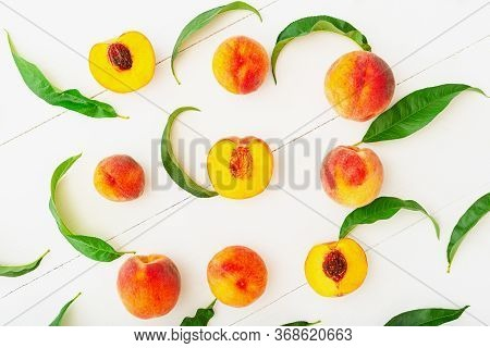 Peaches With Leaves On White Wooden Background With Peach In Halves. Flat Lay Composition With Ripe