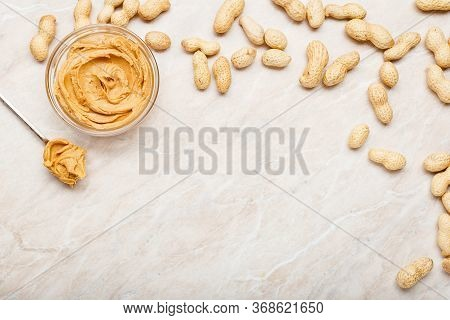 Peanut Butter In Glass Plate With Peanuts In Shell, Spoon With Peanut Butter. Creamy Peanut Paste Fl