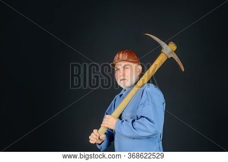 Construction And Building Works. Bearded Man In Uniform Holds Pick Axe. Builder Man Holds Pickaxe. C