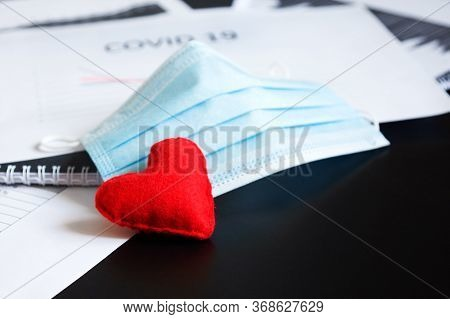 Blue Medical Mask And Felt Heart On Chart For Reducing Incidence Of Morbidity And Mortality. Pandemi