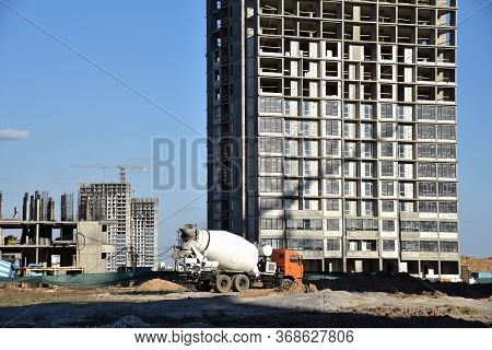 Heavy Mixer Concrete Truck Waiting For To Be Loaded Concrete At A Construction Site. Tower Crane Lif