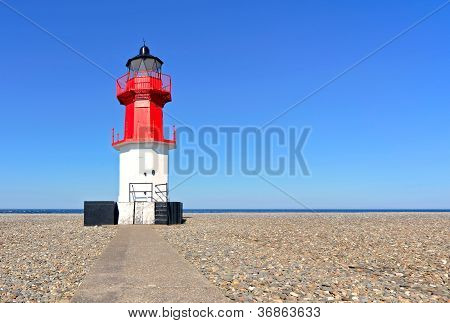 Path to Point of Ayre Lighthouse beach pebbles sea and clear sky in the background. Location Ramsey Isle of Man poster