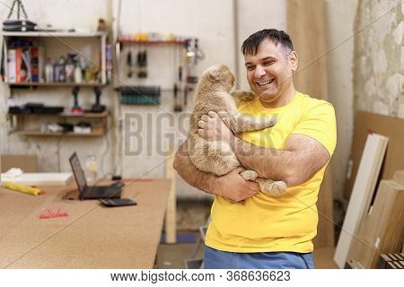 Smiling Carpenter Has A Break To Relax In His Workshop Embracing His Pet. Loving Man In Yellow T-shi