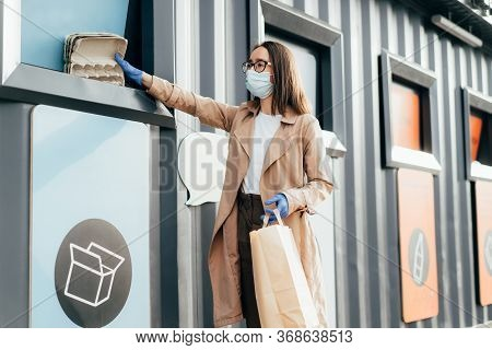Young Woman In Protective Face Mask And Rubber Gloves Throwing Garbage Into Recyclable Trash During