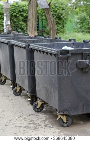 Lined Up Black Plastic Trash Bins. Covered Street Containers For Household Waste On A City Street. A