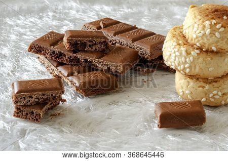 Broken Bar Of Chocolate And Homemade Cookies On A White Shiny Background. A Serving Of Sweet Chocola