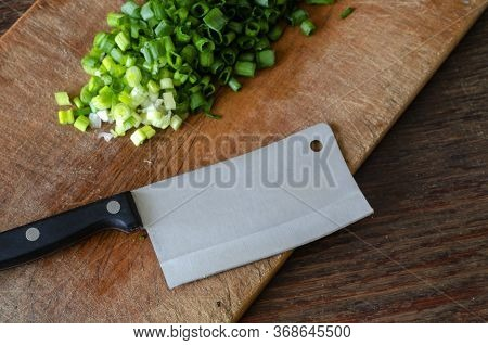 Chopped Lettuce On A Wooden Cutting Board. A Kitchen Hatchet Lies Nearby. The Process Of Cooking Hom