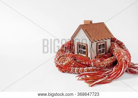 House Wrapped In A Scarf Isolated On White,  Time To Warm The Home. Thermal Insulation Concept.  Toy