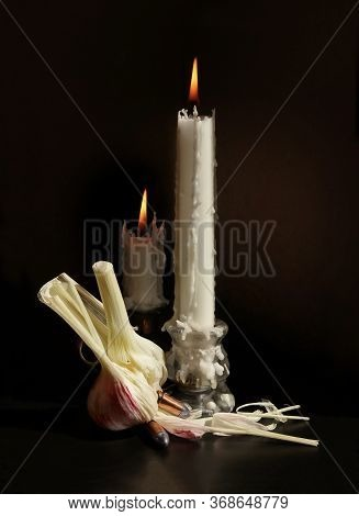 Still Life With Two Candlesticks With Burning Candles, Garlic Bulb And Two Handgun Cartridges With S
