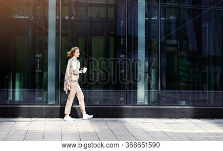 Business Woman In Beige Suit Walking On City Street Near Building Or Skyscraper With Glass Windows,