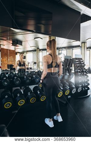 The Concept Of A Healthy Lifestyle And Workouts In The Gym. Blonde Girl In Sportswear Engaged In The