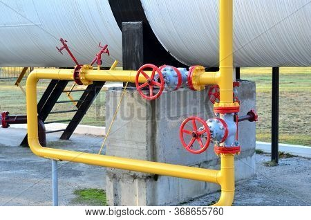 Industrial Piping With Steel Flanges And Bolts On Oil Field. Fuel Pipes Valves And Crude Pipelines.