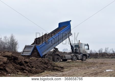Dump Truck Dumps Its Load Of Sand And Ground On Construction Site For Road Construction Or For Found