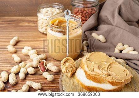 Peanut Butter In Spoon Near Creamy Peanut Paste In Open Glass Jar, Slice Of Peanut Butter Bread, Toa