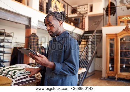 Male Owner Of Fashion Store Using Digital Tablet To Check Stock In Clothing Store