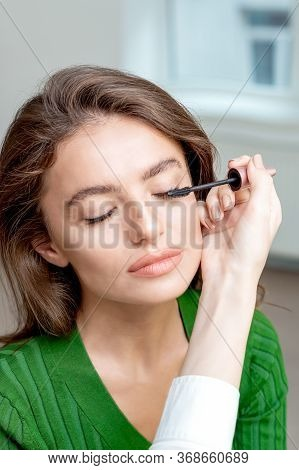 Makeup Artist Applies Mascara On Eyes Of Young Woman.