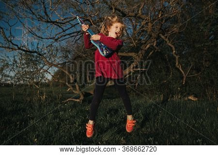 Cute Adorable Young Girl Playing Guitar Toy Outdoor. Girl Pretending To Be A Rock Music Star. Adorab