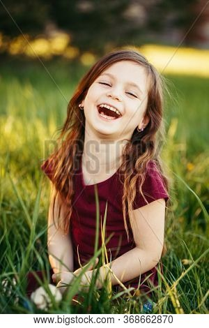 Closeup Portrait Of Funny Smiling Laughing Young Caucasian Girl Outdoor. Cute Adorable Kid Child Hav