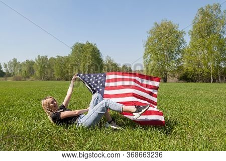 Russian Girl Blond Is Fooling Around On The Grass, Lying Down Reclining, Holding The Developing Flag