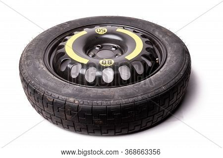 Black Spare Tire On A White Isolated Background In A Photo Studio With An Aluminum Disk And A Rubber