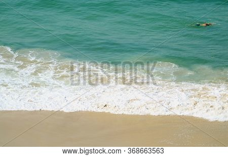 Man Swimming In The Wavy Atlantic Ocean, Copacabana Beach, Rio De Janeiro, Brazil
