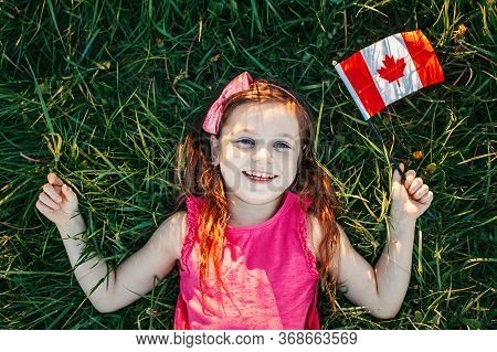 Adorable Cute Happy Caucasian Girl Holding Canadian Flag. Smiling Child Lying On Grass In Park Holdi