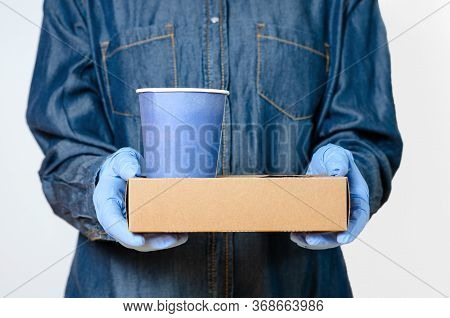 Person With Surgical Gloves Who Brings Coffee To The Door Or Office . Concept Regarding Hygiene And