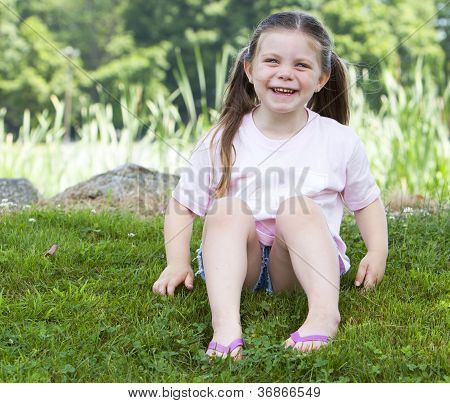 Young Girl Laughing In The Grass