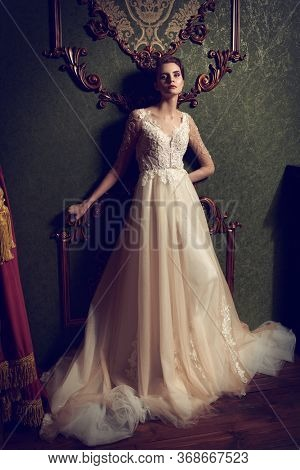 Full length portrait of a magnificent young woman in elegant white long dress. Luxurious dark apartments.  Wedding fashion.