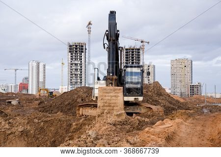 Black And White Excavator During Earthworks At Construction Site. Backhoe Digging The Ground For The